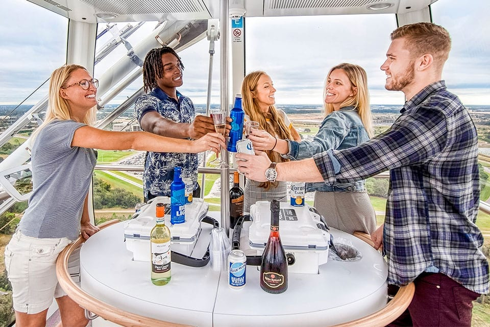 Group of people toasting drinks inside of the Wheel capsule