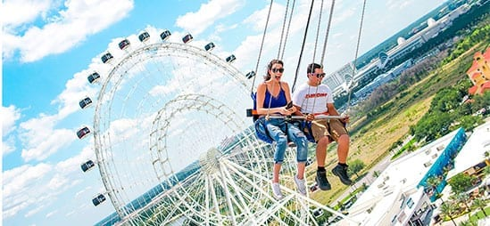 couple riding the Star Flyer with the Wheel in the background