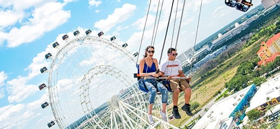 Couple riding the Orlando StarFlyer in front of The Wheel